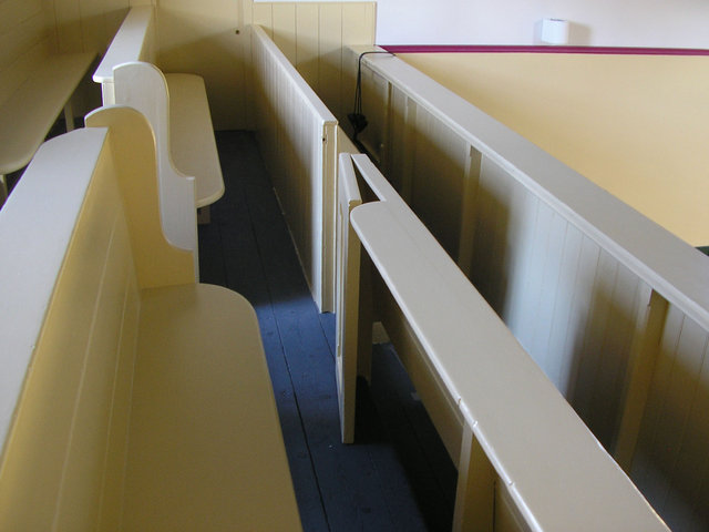 The balcony features original, church-style, pews.